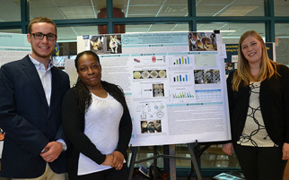 Three students standing in front of a poster presentation.