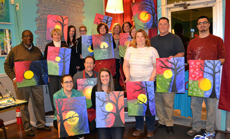 Alumni and friends displaying their work from an alumni mixer at a paint and sip night.