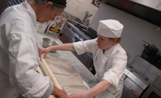A culinary student and faculty member work in a kitchen lab making bread.