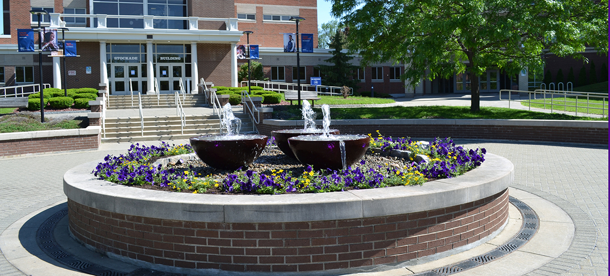 Fountain in the center of the Quad at SUNY Schenectady, flowers growing around it.